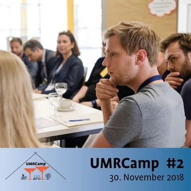 Menschen in einer Gesprächsrunde, Schriftzug UMRCamp #2, 30. November 2018