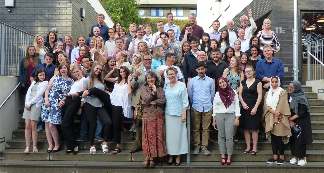 Etwa 60, vornehmlich junge Menschen, augenscheinlich unterschiedlicher Nationalitäten und Religionen, posieren herumalbernd für ein Gruppenfoto auf Treppenstufen.