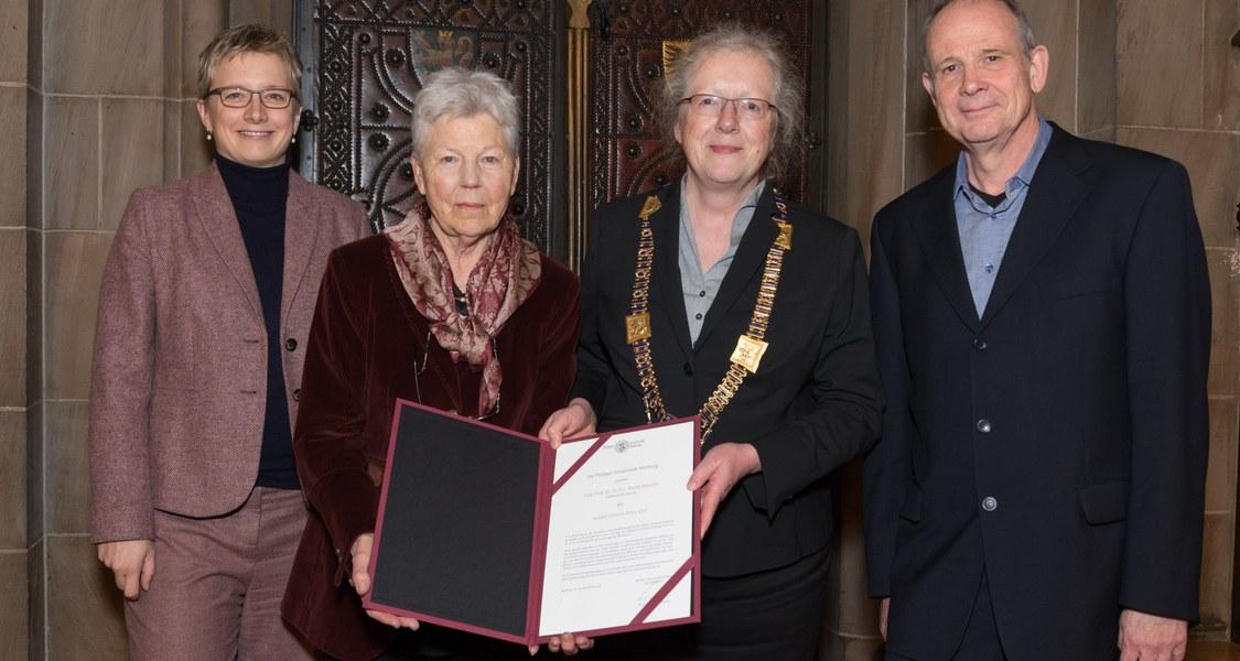 Gruppenfoto mit Preisträgerin und Urkunde