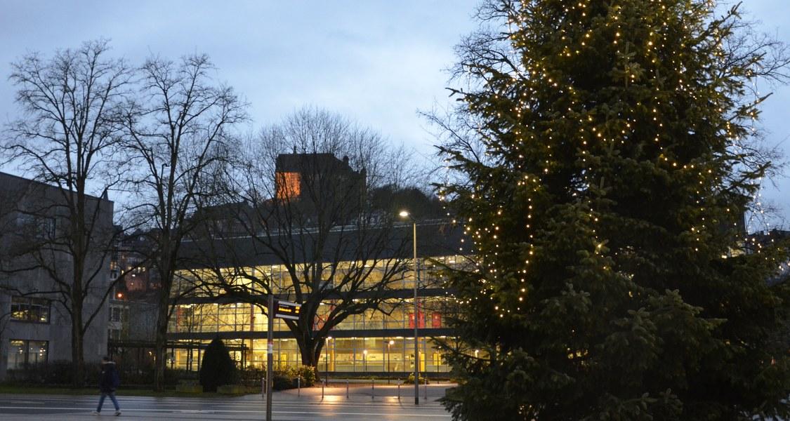 Hörsaalgebäude mit Weihnachtsbaum auf dem Vorplatz der Stadthalle