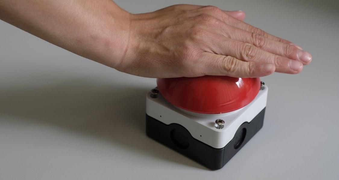 Hand drückt auf roten Buzzer