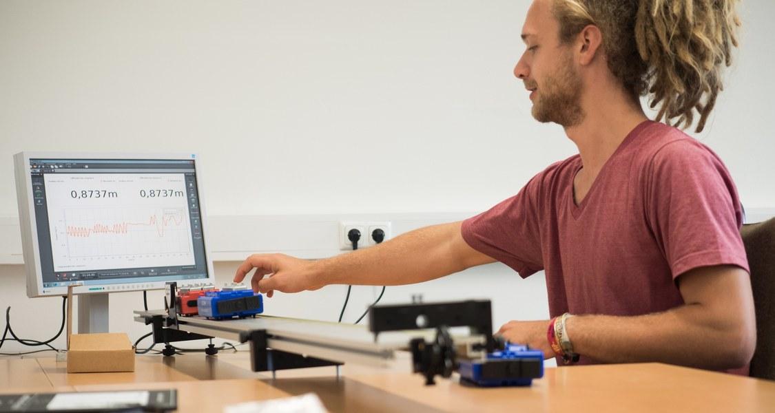 Student sitzt am Tisch mit einem Computer und zwei kleinen Wagen, die auf dem Tisch auf einer Bahn fahren
