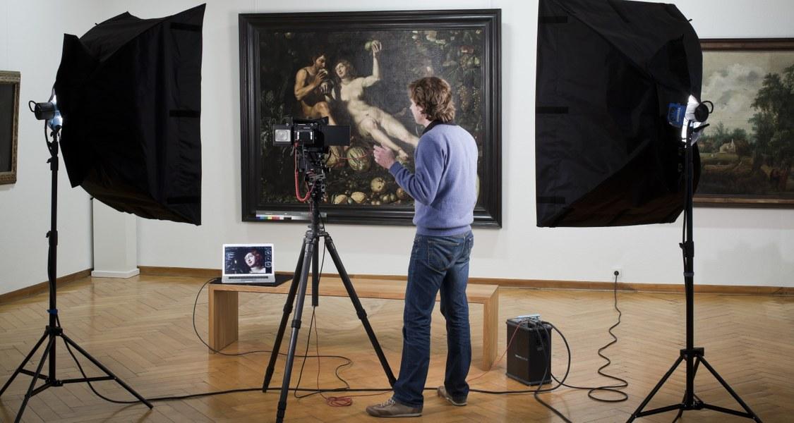 Fotograf mit Scheinwerfern vor Gemälde in einem Raum