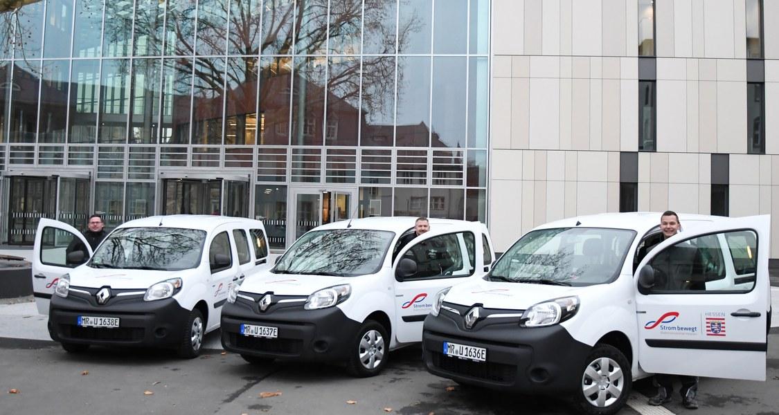 Drei Mitarbeiter des Dezernats Gebäudemanagement und Technik – Christoph Bromm und Markus Reitz (Sicherheitstechnik) sowie Mike Schleich (Stromversorgung) – nehmen die drei Elektroautos der Philipps-Universität in Betrieb.