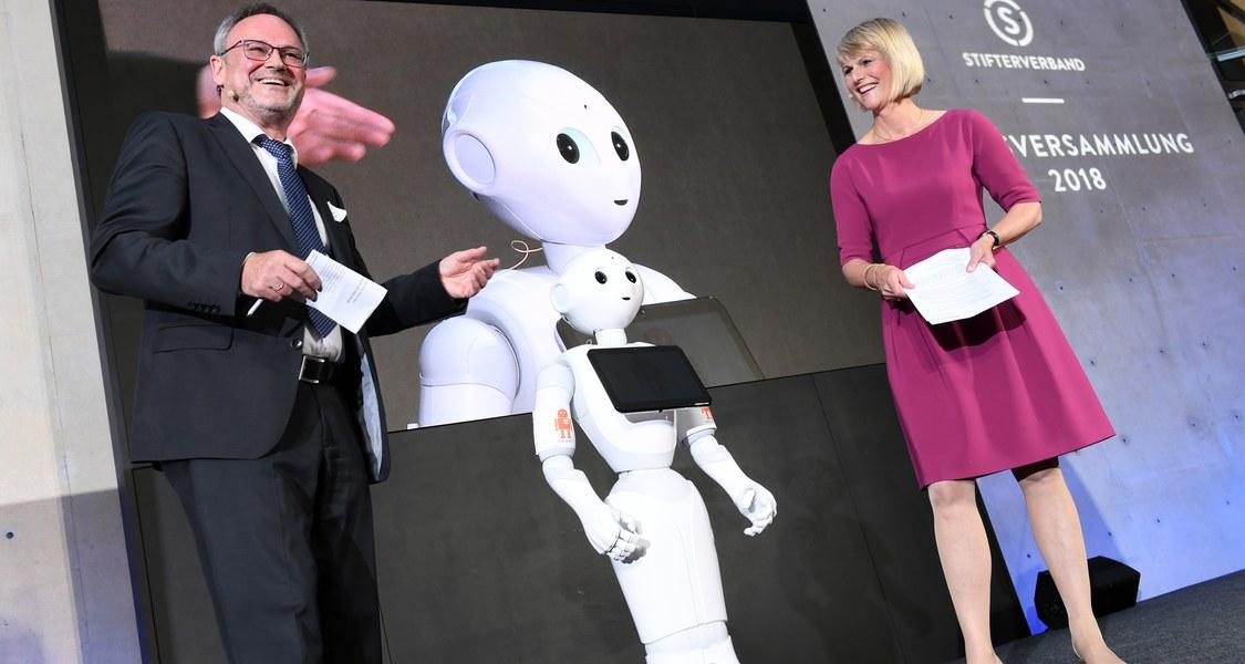 Podiumsfoto mit zwei Personen (Jürgen Handke und Gundula Gause) und humanoidem Roboter Yuki in der Mitte