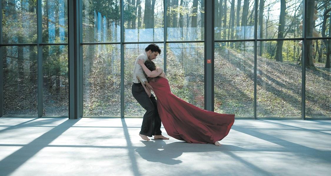 Tänzerin im roten langen Kleid an Tänzer gelehnt vor Fensterfront mit Wald im Hintergrund