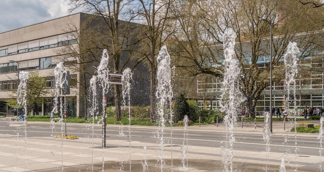 Wasserspiel - Wasserfontänen kommen aus Platz vor Erwin-Piscator-Haus, im Hintergrund Hörsaalgebäude
