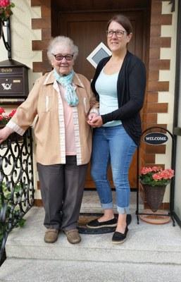 jüngere Frau hilft älterer Frau eine Treppe hinunter vor einer Haustür