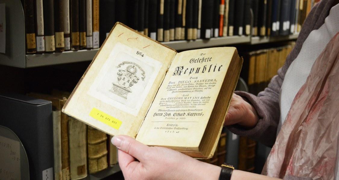 Foto vom ersten Buch, das in die neue Universitätsbibliothek zieht