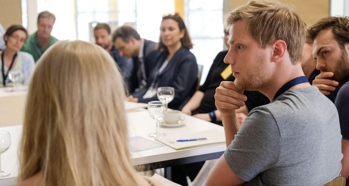Gruppenfoto, Menschen sitzen um Tisch und sprechen miteinander