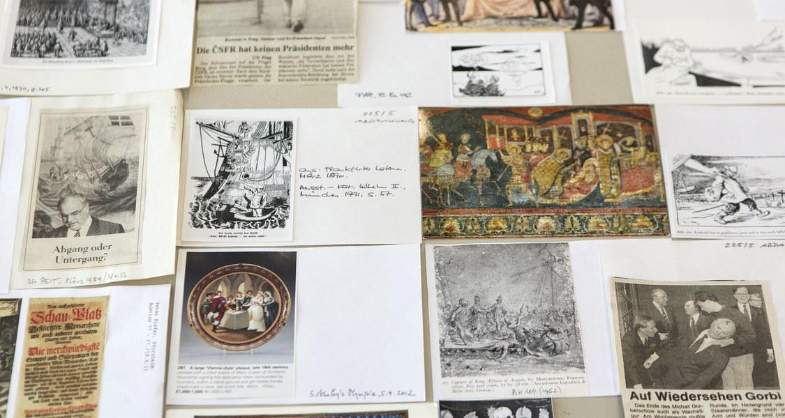 viele einzelne Bilder und Zeitungsausschnitte mit handschriftlichen Erläuterungen zur Herkunft