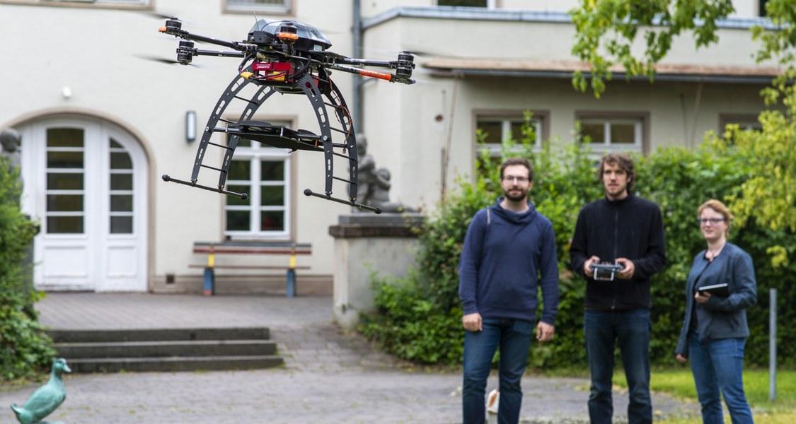 Studierende im Hintergrund, fliegende Drohne im Vordergrund