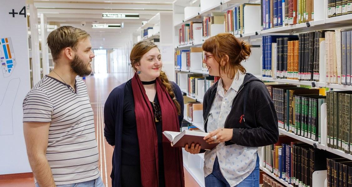 Studierende unterhalten sich in der Universitätsbibliothek