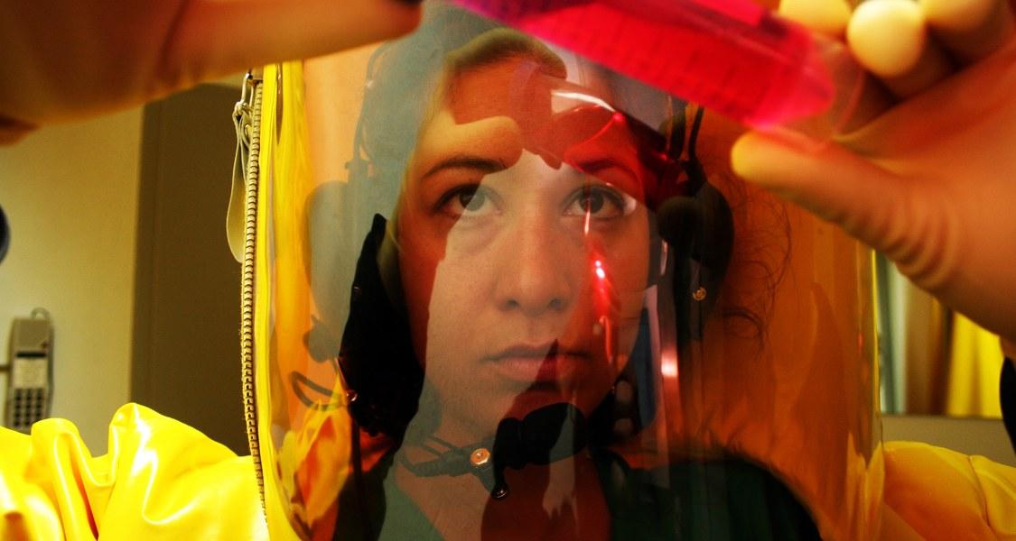 Frau in Schutzkleidung hält Reagenzglas hoch