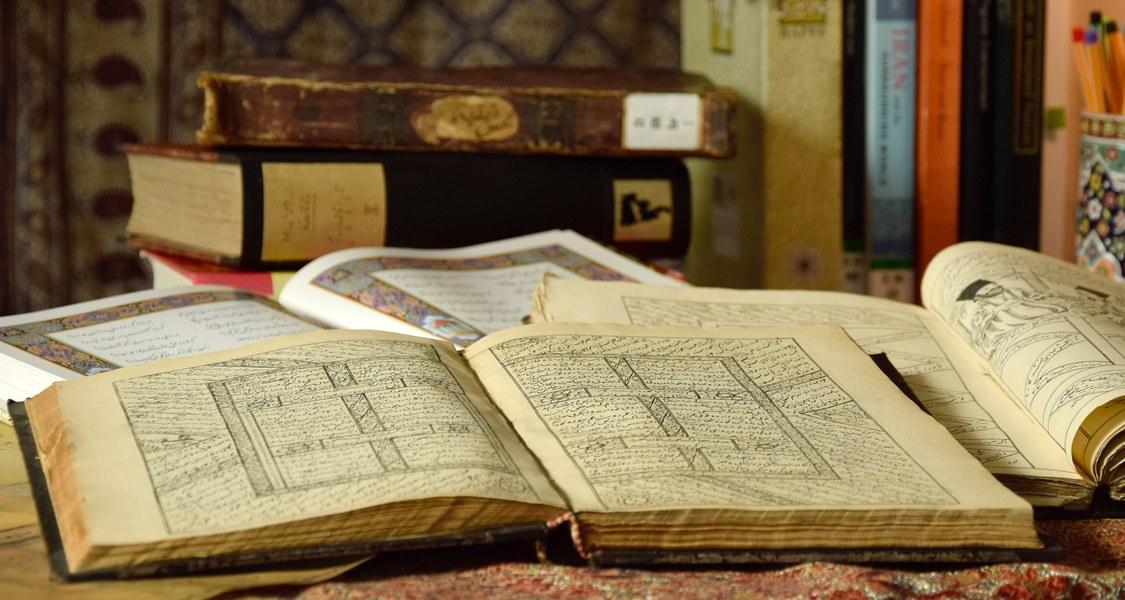 Aufgeschlagene Bücher auf einem Tisch, im Hintergrund bunte Stifte in einem Stiftehalter