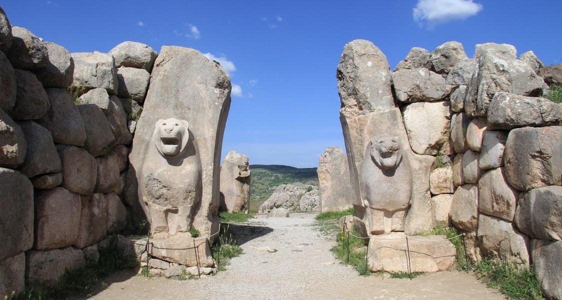 Steinerne Löwen zu beiden Seiten eines Weges blicken Betrachter an, im Hintergrund Horizont