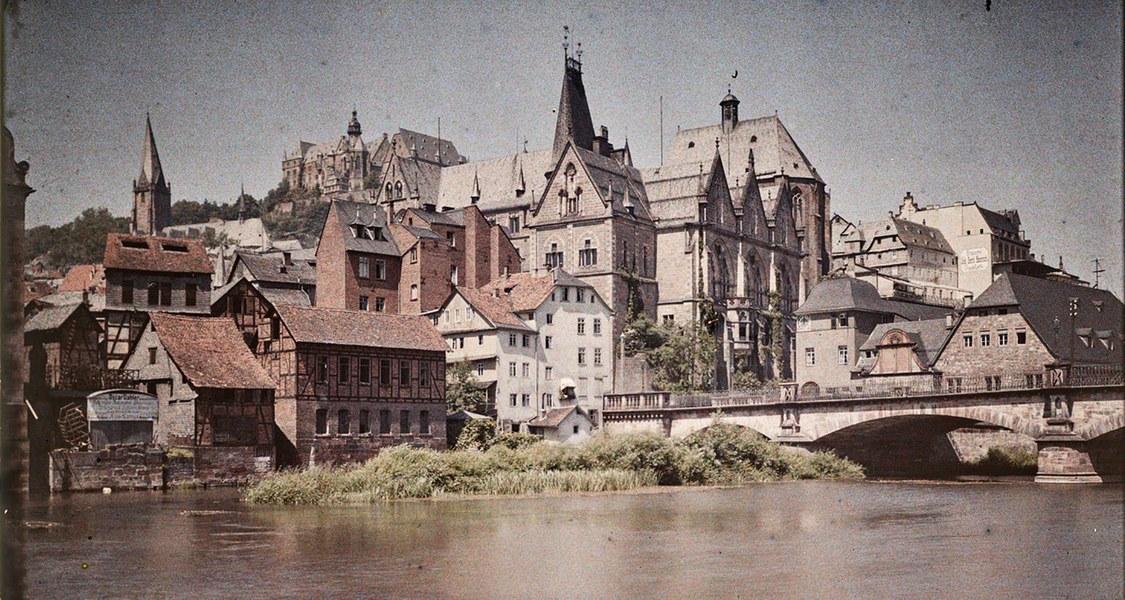 Farbaufnahme mit Blick von Weidenhausen auf die Weidenhäuser Brücke, im Hintergrund die Alte Universität und die Oberstadt mit Schloss um 1910