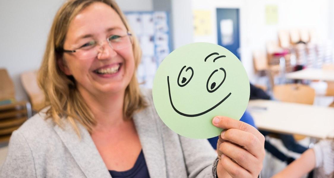 Frau hält runden Zettel mit Smiley in die Kamera