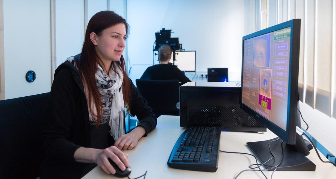 Frau vor Bildschirm im Hintergrund Mann vor Bildschirm