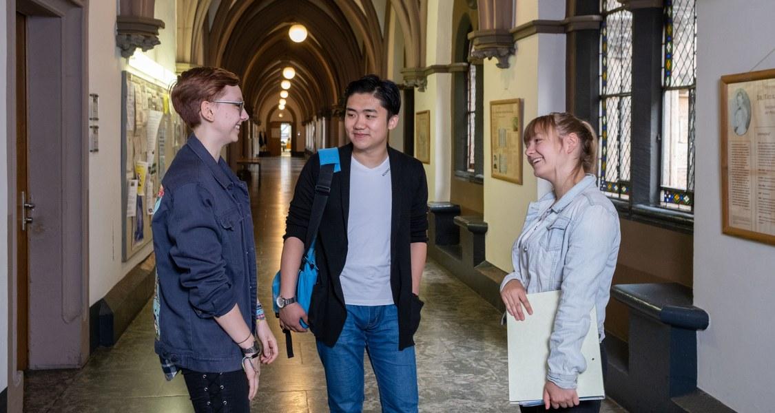 drei Studierende im Flur der Alten Universität