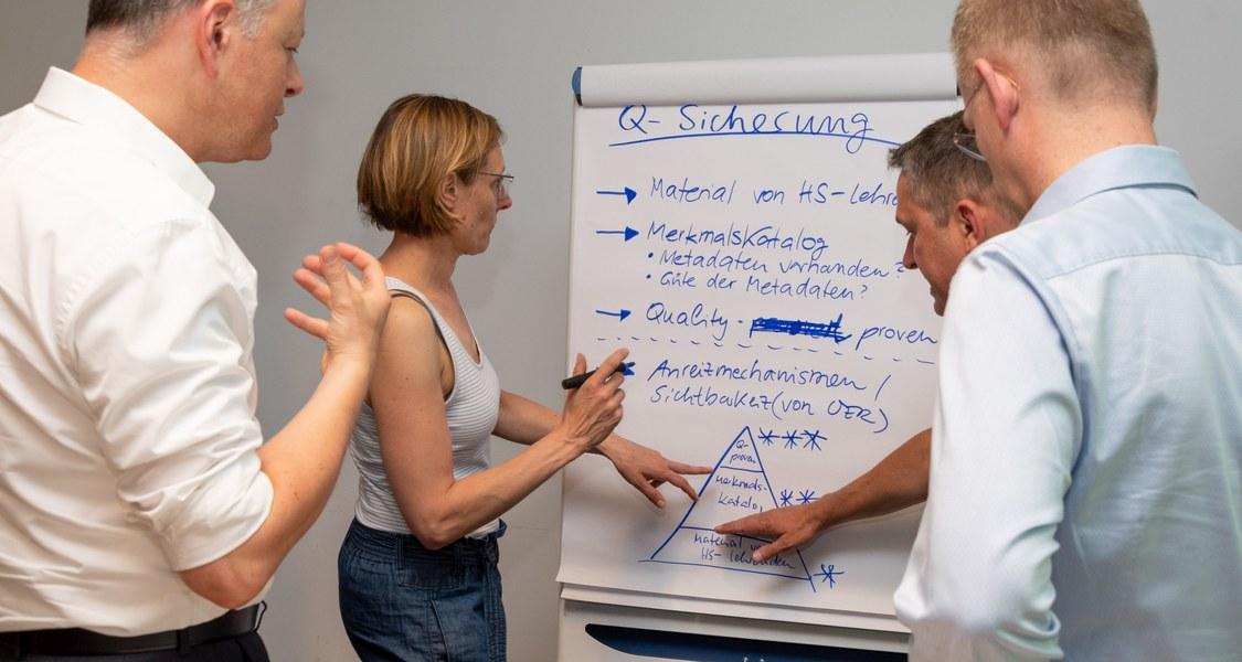 Gruppenfoto mit Flipchart zum Thema Qualitätssicherung