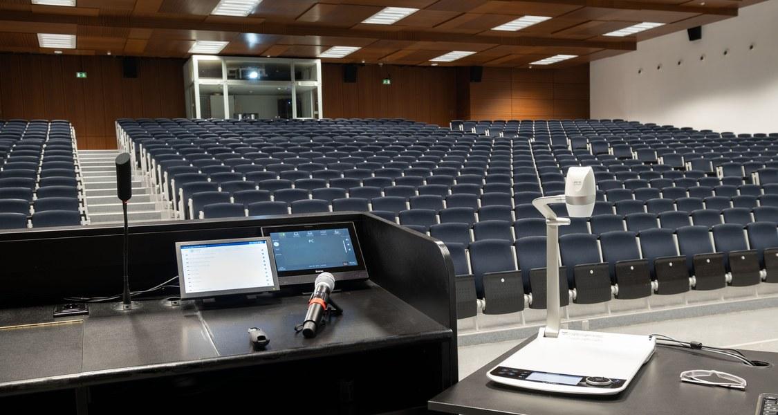 Blick vom Rednerpult im Audimax auf leere Stuhlreihen, im Vordergrund Mikrofon
