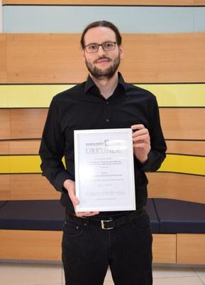 Halbtotale des Preisträgers mit Urkunde
