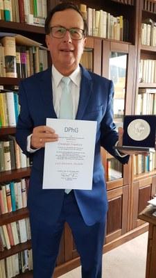 Halbtotale mit Urkunde und Medaille vor einem Bücherregal