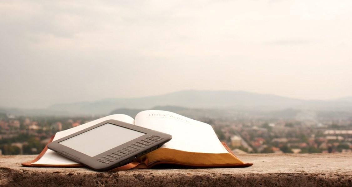 Foto von einem Buch und einem E-Reader