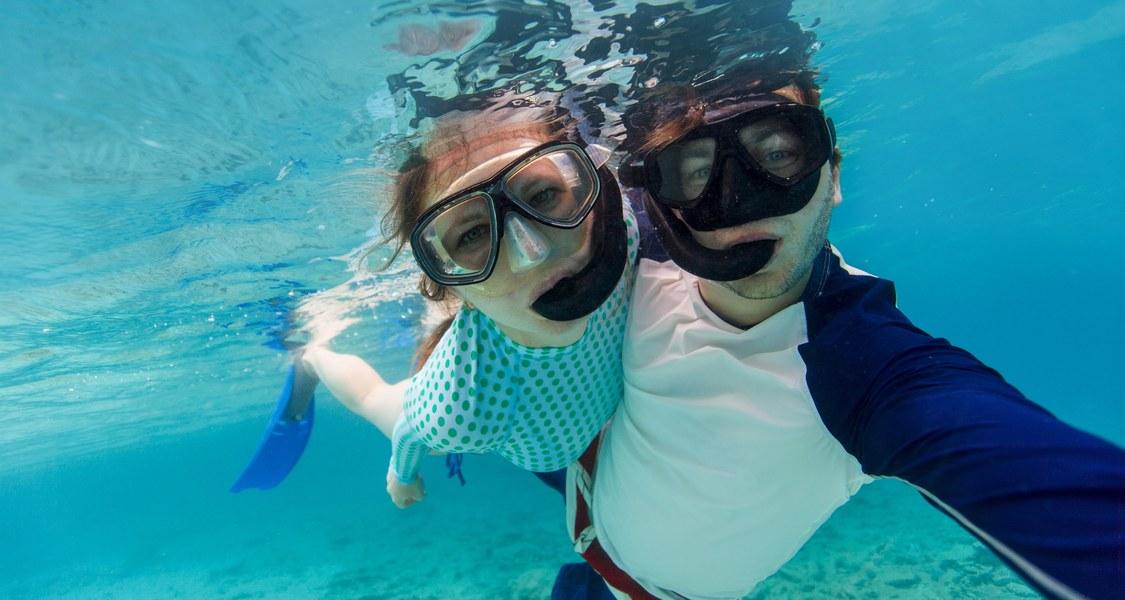 eine Frau und ein Mann mit normaler Straßenkleidung und mit Taucherbrille und Schnorchel schauen unter Wasser in die Kamera