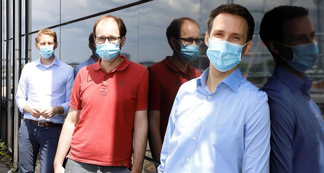Gruppenfoto vor Glasfassade, alle Personen tragen Mund-Nasen-Bedeckung und lehnen an der Glasfassade
