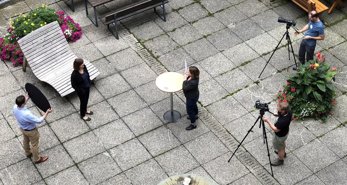 Links stehend Prof. Beinhauer-Köhler, in der Mitte des Bildes Interviewerin, rechts zwei Personen mit Kameras