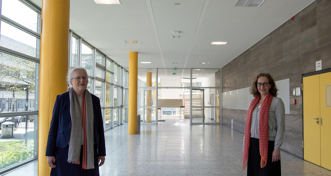 zwei Personen in einem langen leeren Flur des Hörsaalgebäudes mit Glasfront links