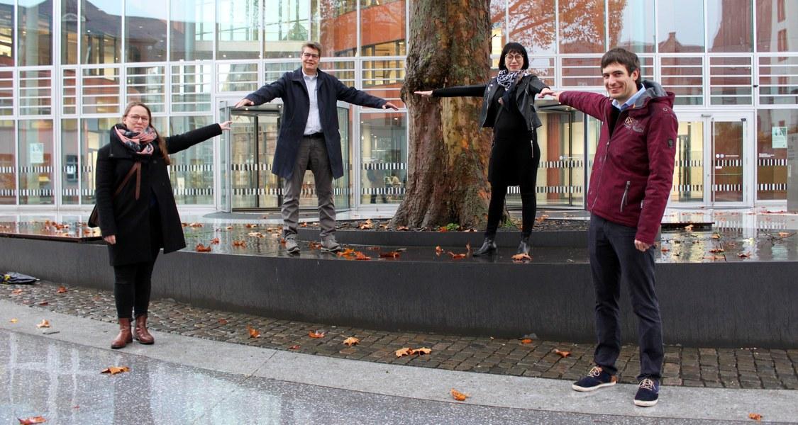 Gruppenfoto vor Haupteingang der UB mit großer Platana in der Mitte des Bildes