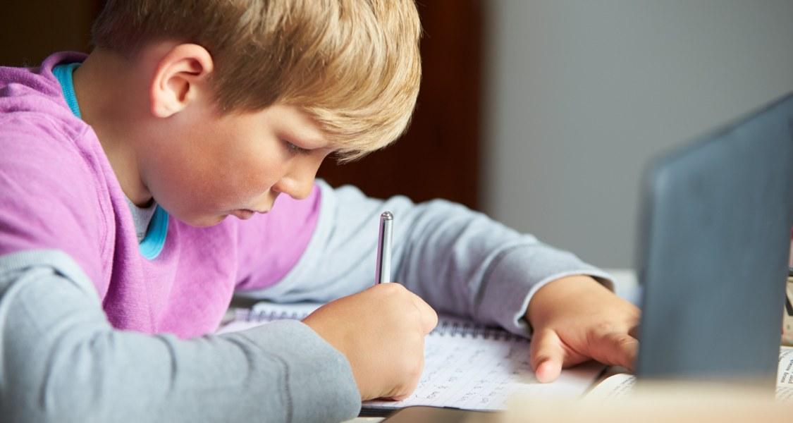 Foto eines Kindes, das Hausaufgaben macht