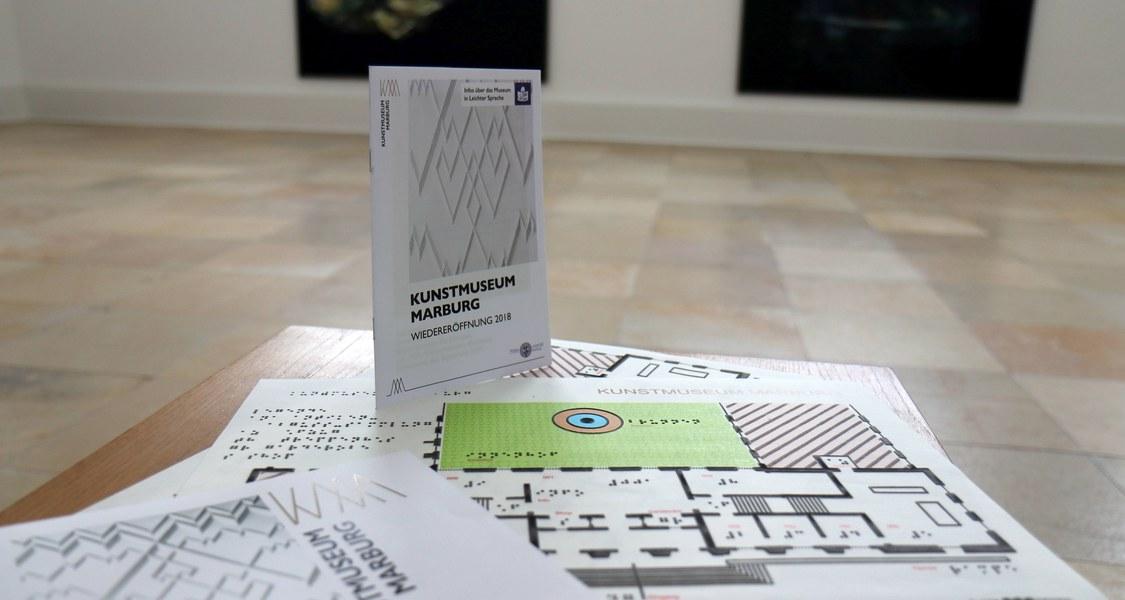 Blick in Museumsraum mit Bildern im Hintergrund, im Vordergrund Tastplan des Museums und Broschüre in leichter Sprache auf einer Holzbank