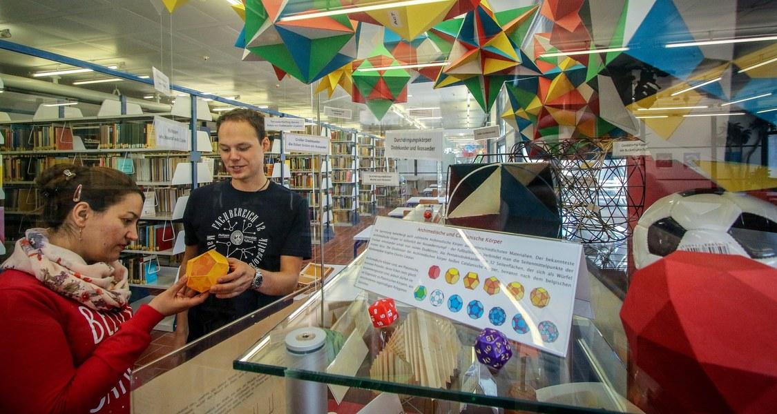 ein Student (rechts) und eine Studentin (links) schauen sich ein mathematisches Modell vor Regalreihen in der Bibliothek an