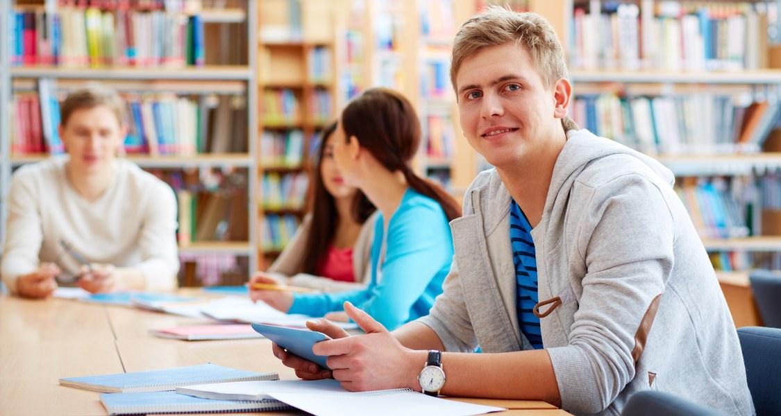 mehrere Personen in einer Bibliothek an einem Tisch