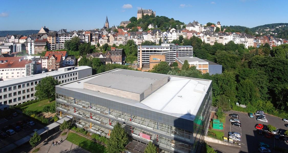 Foto mit Dach des Hörsaalgebäudes und Panorama der Oberstadt im Hintergrund