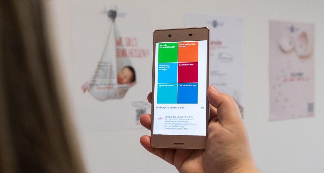 Handy mit Marvin-Funktionen, im Hintergrund Poster der einzelnen Marvin-Schritte