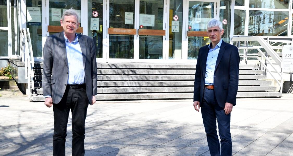 Foto mit zwei Personen vor dem Hörsaalgebäude der Philipps-Universität