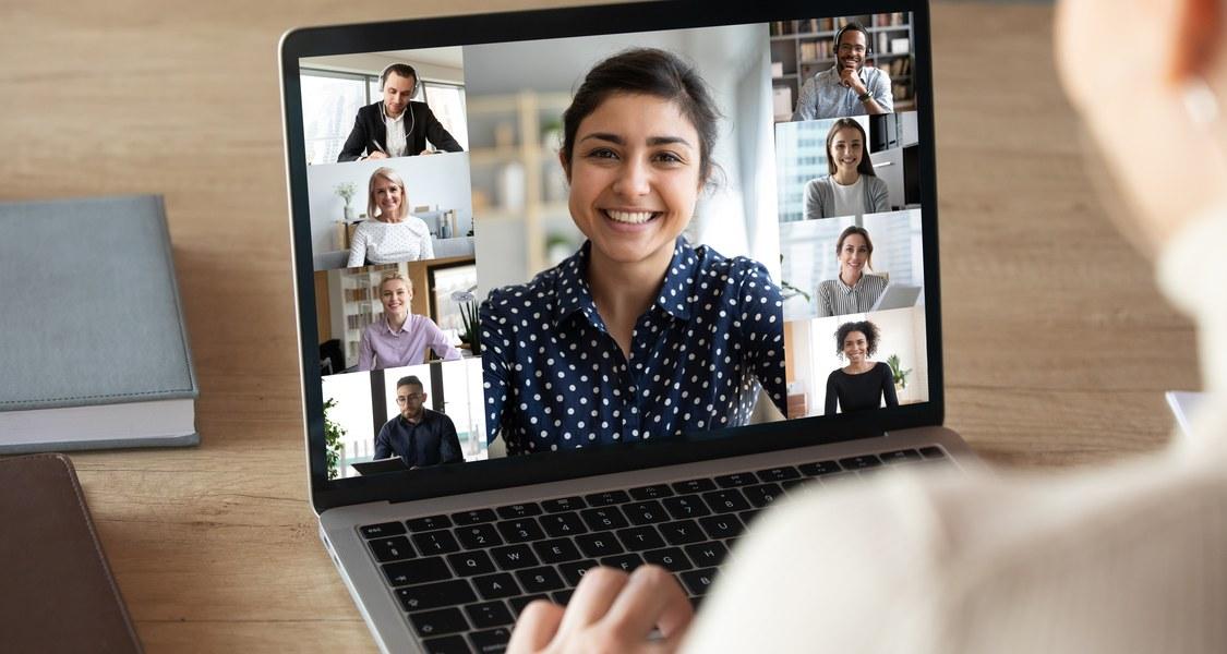 junge Frau sitzt vor Laptop, auf dessen Bildschirm verschiedene Gesichter in einer Collage wie bei einer Videokonferenz zu sehen sind