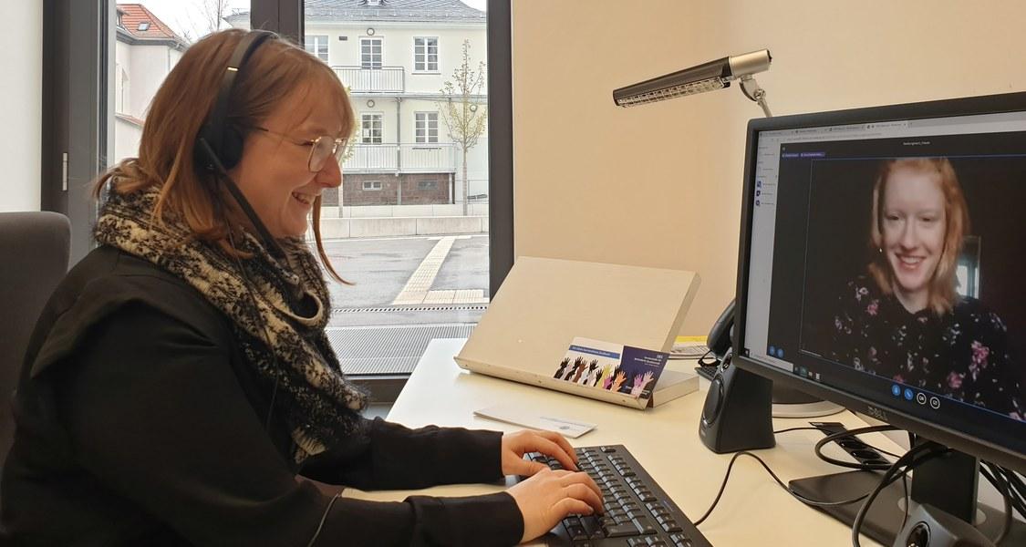 Frau mit Headset sitzt vor Bildschirm, auf dem eine andere Frau im Videocall zu sehen ist