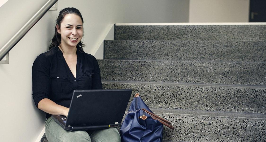 Lachende Studentin sitzt mit einem Laptop auf einer Treppe