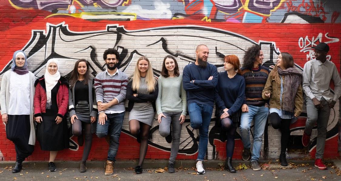 Studierende lehnen an einer Wand, die mit Graffiti besprüht ist.