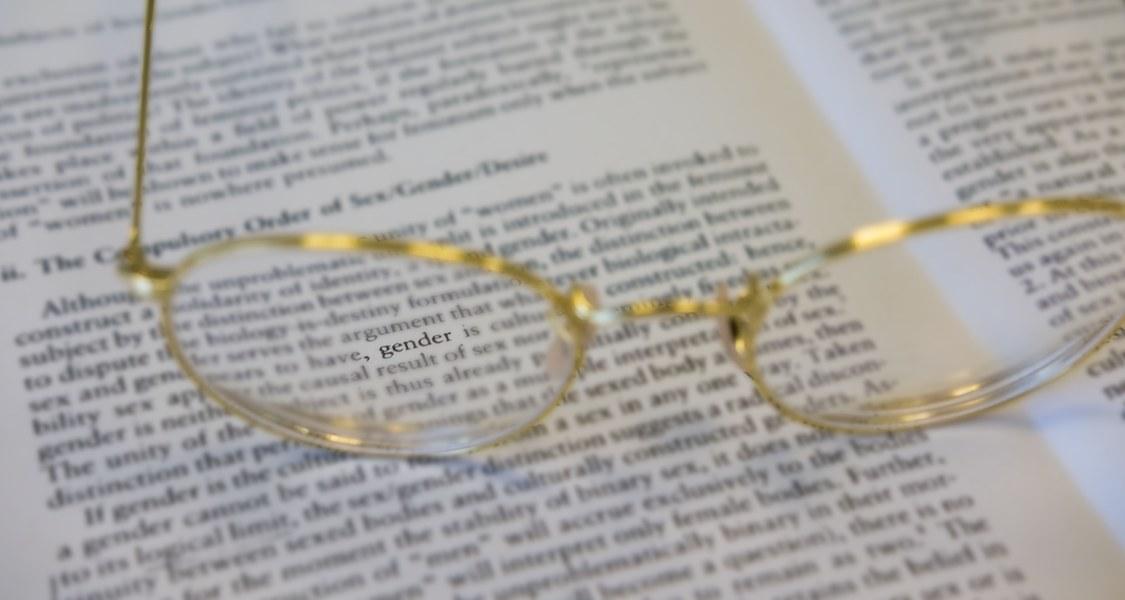 """Brille auf einer Buchseite, das Wort """"Gender"""" ist im Zentrum eines Brillenglases zu sehen"""