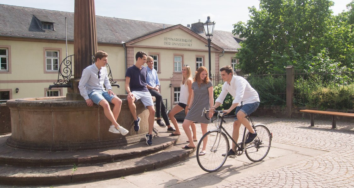 Studierende am Brunnen am Plan Fahrrad