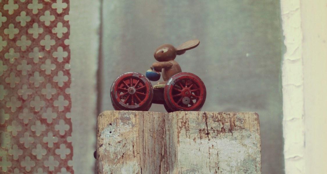 Blick in ein Fenster, in dem eine kleine hölzerne Osterhasenfigur mit einem Korb in der Hand auf einem Vierrad sitzt