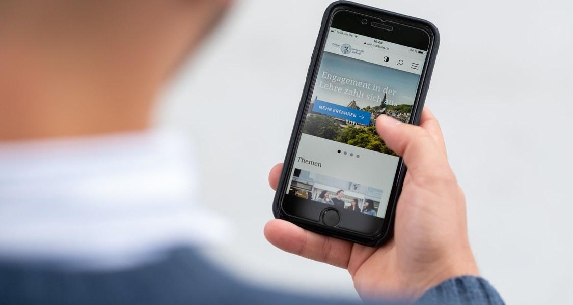Mann hält ein Smartphone in der Hand.