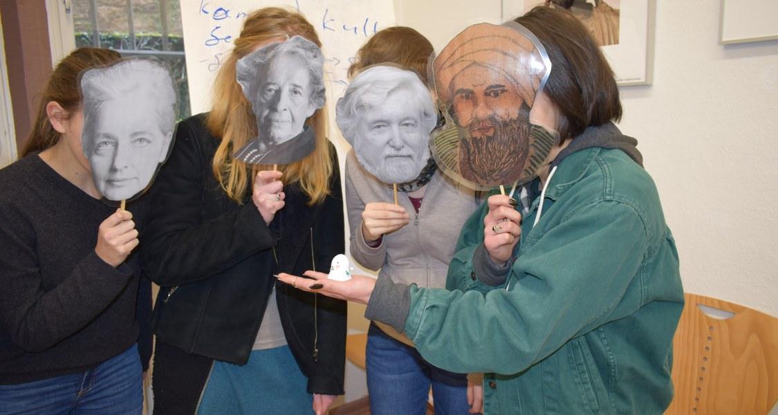 Eine Gruppe von Studierenden steht in einem Halbkreis um ein Objekt, einen kleinen Plastik-Geist herum, sichtbar im Gespräch. Vor den Gesichtern halten sie sich Masken von zentralen Theoretikern und Theoretikerinnen des Faches.